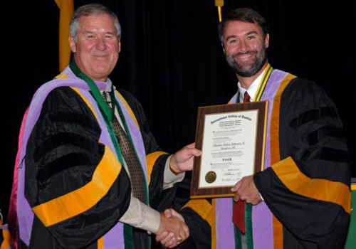 Earning Fellowship in the International College of Dentists with Dr. Roberson's father.